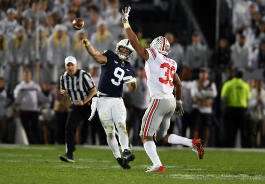 Penn State quarterback Trace McSorley  passes as Ohio State linebacker Malik Harrison defends in the second quarter at Beaver Stadium.