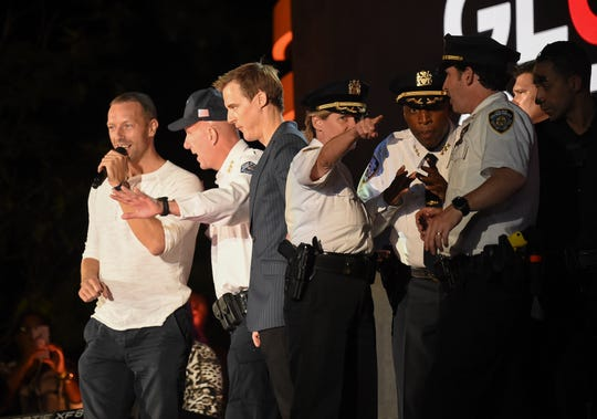 Police huddle onstage as Chris Martin calms the crowd at Global Citizen Festival in Central Park. Fearing possible gunshots, it took only the collapse of a police barrier at the show Saturday to send thousands of spectators fleeing in panic.