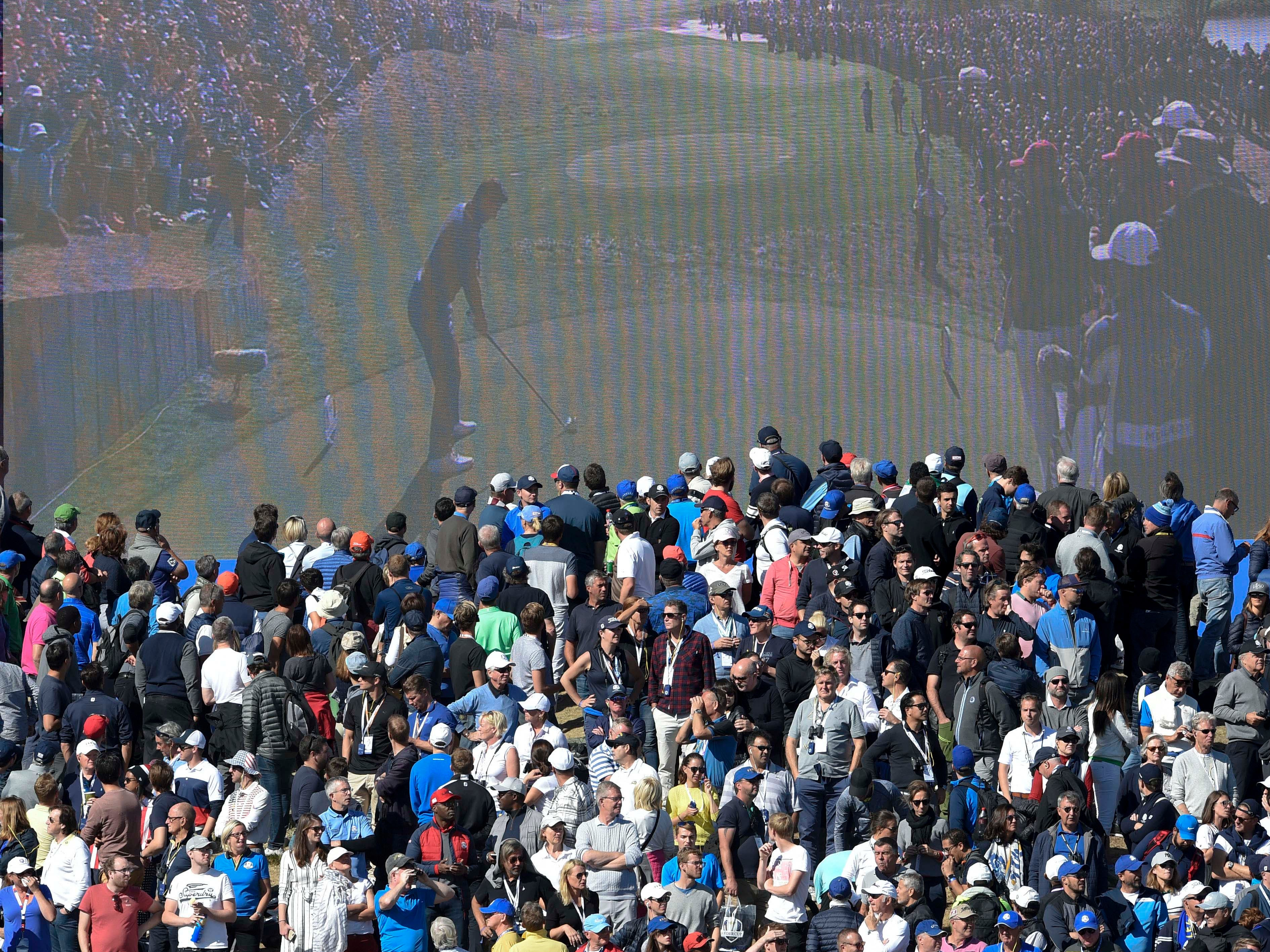 Fans watch the video board on the first fairway during the Sunday singles matches.