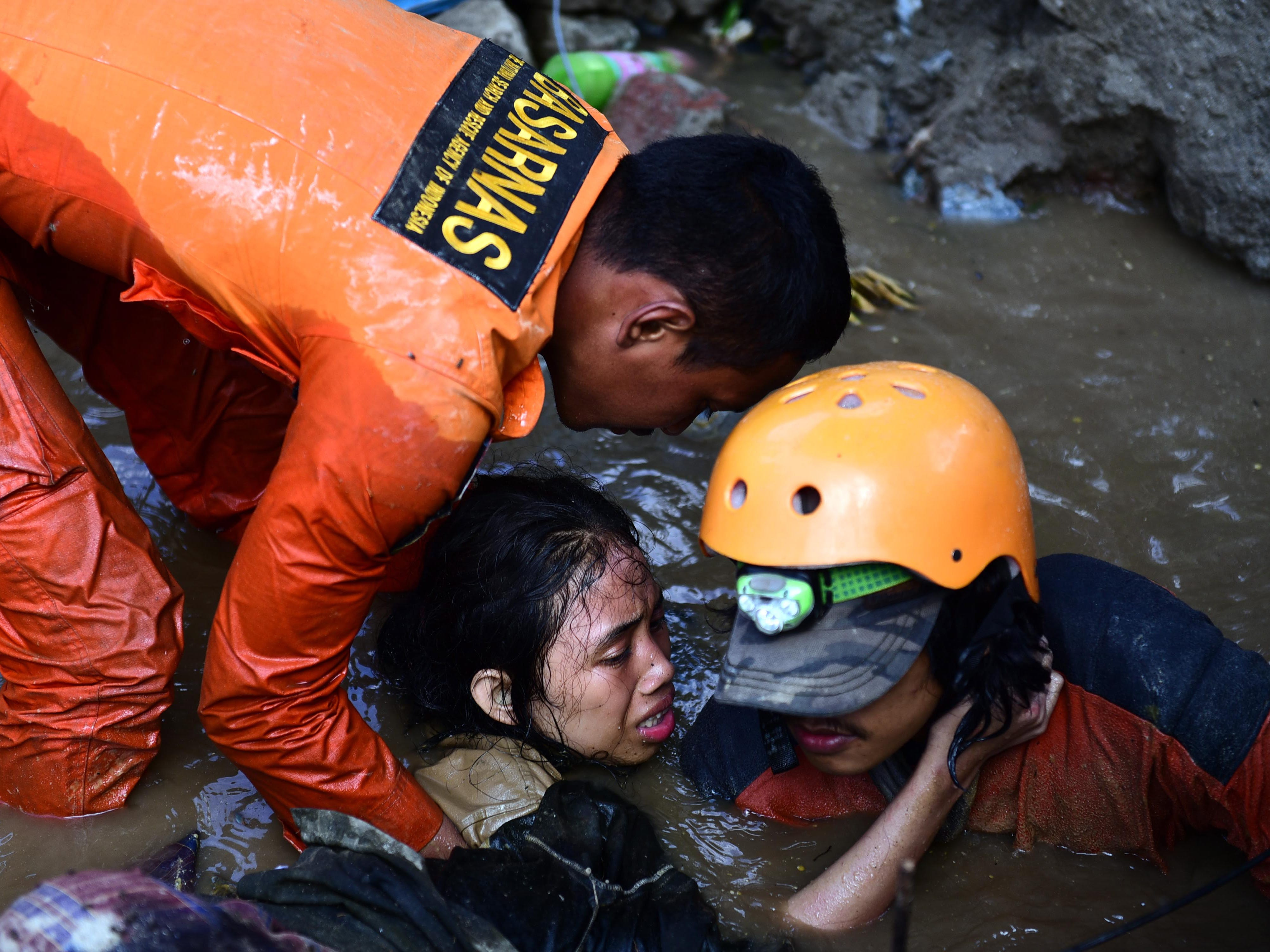 Rescuers try to free a 15-year-old earthquake survivor, Nurul Istikhomah, from the flooded ruins of a collapsed house in Palu, Central Sulawesi, Indonesia, Sept. 30, 2018. Istikhamah had been trapped in water for two days. Authorities said hundreds of people have died as a result of a series of powerful earthquakes that hit Central Sulawesi and triggered a tsunami on Sept. 28, 2018.