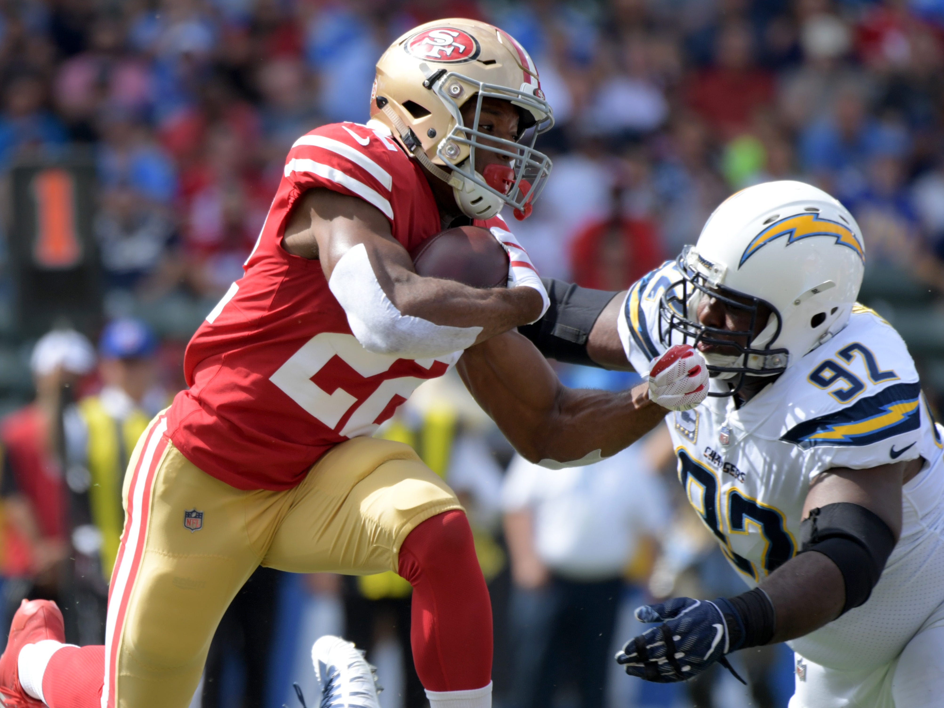 San Francisco 49ers running back Matt Breida carries the ball as Los Angeles Chargers defensive tackle Brandon Mebane makes the tackle during the first half at StubHub Center.