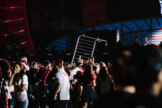 People react after a fence fell, causing panic and creating a massive stampede at Global Citizen Festival on Saturday in New York.