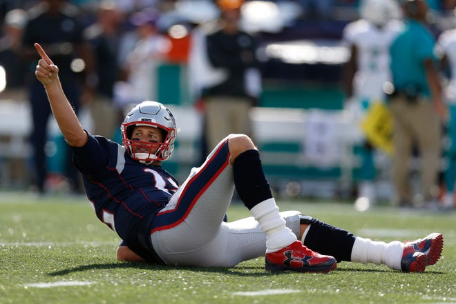 New England Patriots quarterback Tom Brady (12) reacts after throwing a touchdown during the third quarter against the Miami Dolphins at Gillette Stadium.