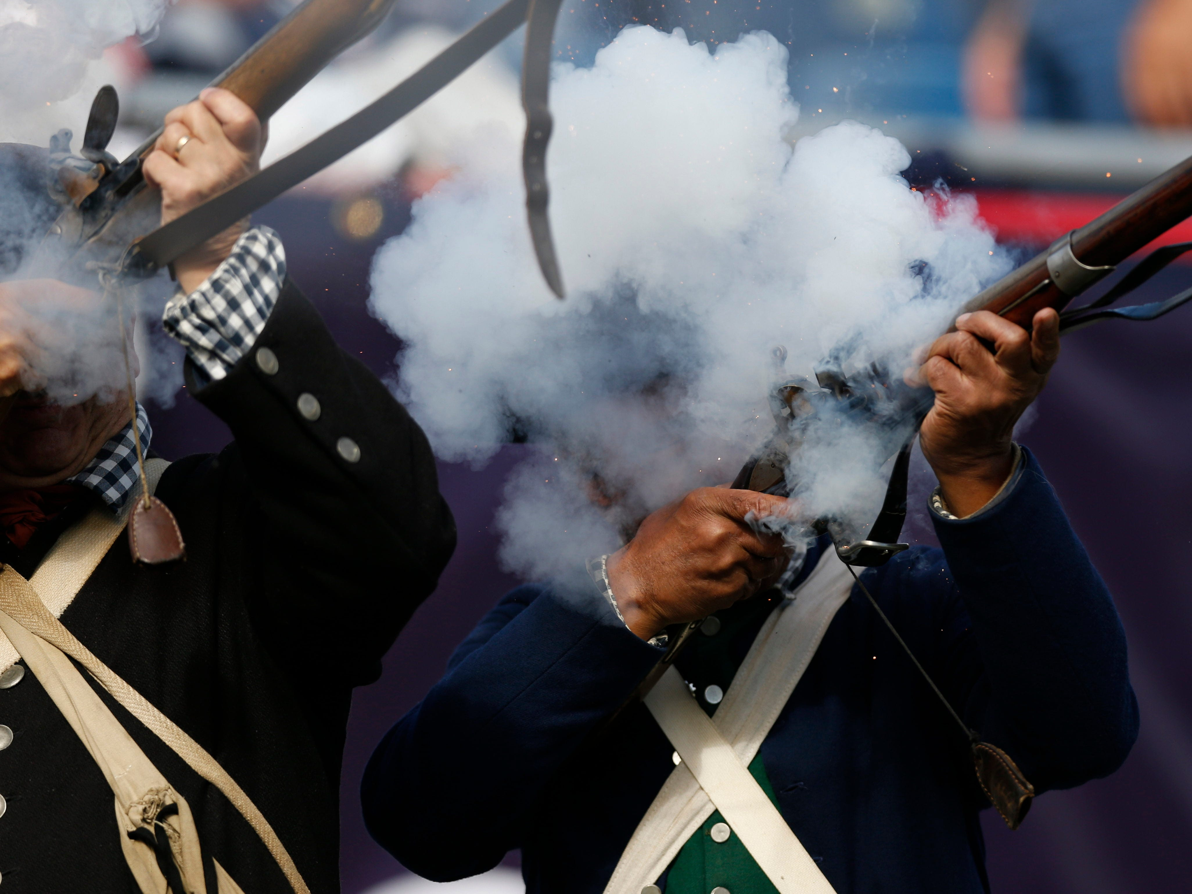 A member of the New England Patriots end zone militia fires a shot after a touchdown during the second quarter against the Miami Dolphins at Gillette Stadium.