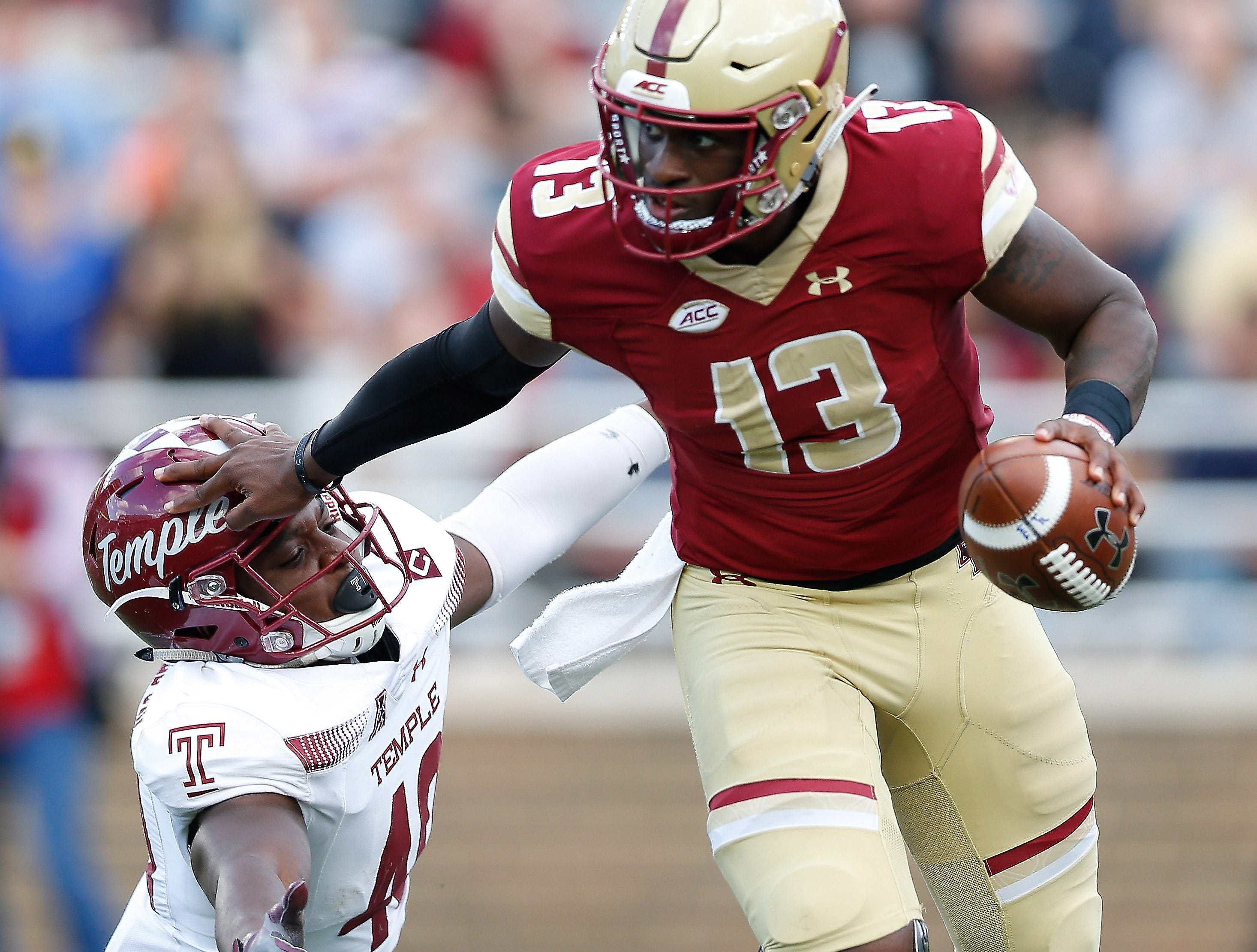 Boston College Eagles quarterback Anthony Brown (13) evades the tackle of Temple Owls linebacker Todd Jones (40) during the second half at Alumni Stadium.
