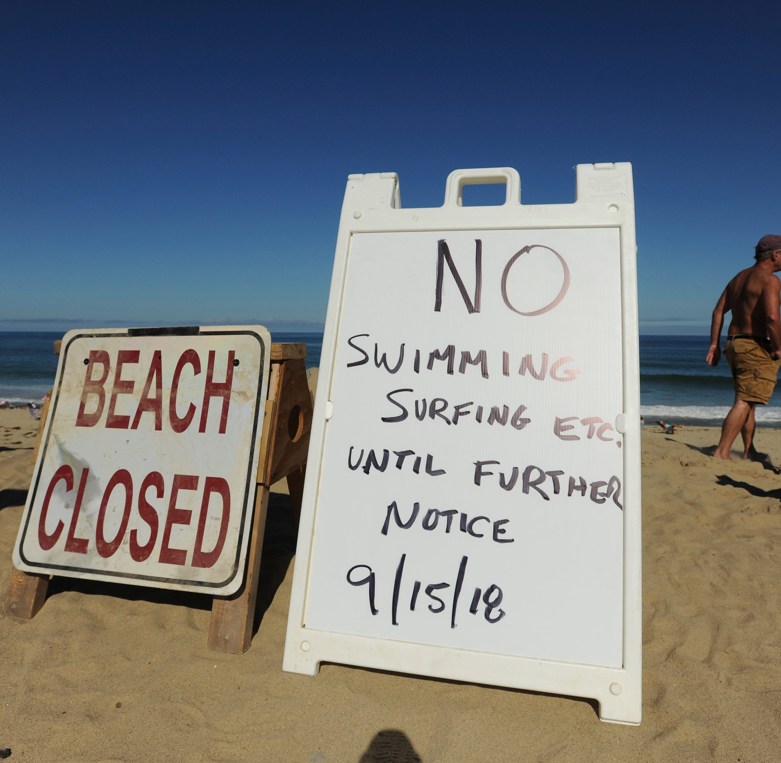 Two signs at the top of the dune at Newcomb Hollow Beach alert visitors that the beach is closed to swimming, Saturday, Sept. 15, 2018, in Wellfleet, Mass.