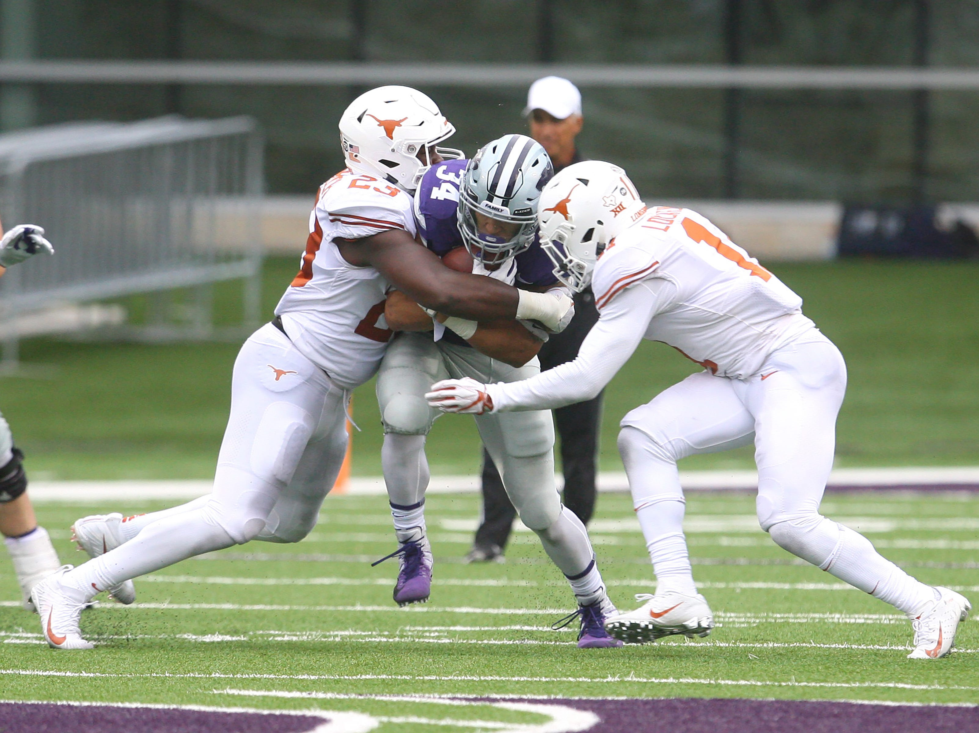 Kansas State Wildcats running back Alex Barnes (34) is tackled by Texas Longhorns linebacker Jeffrey McCulloch (23) and defensive back P.J. Locke III (11) during the third quarter at Bill Snyder Family Stadium.