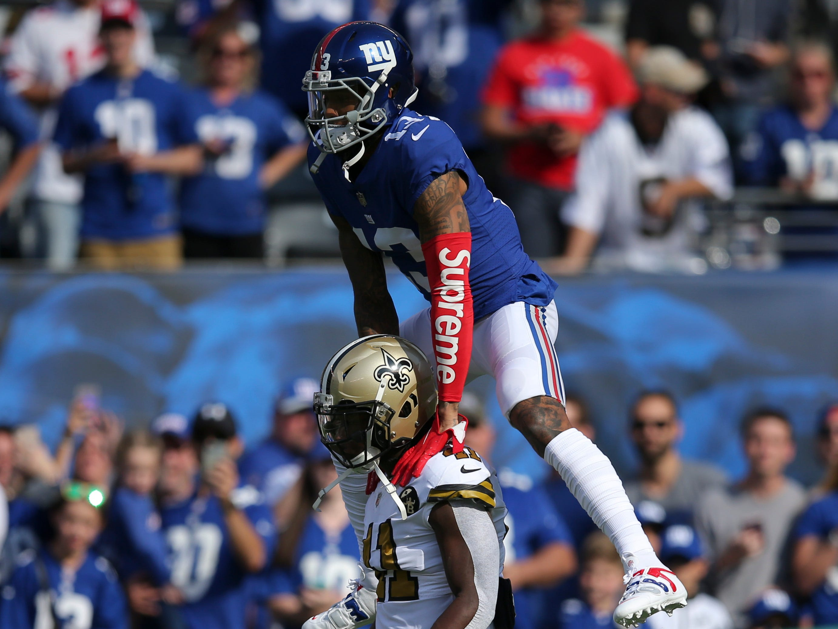 New York Giants wide receiver Odell Beckham Jr. leaps over New Orleans Saints running back Alvin Kamara before a game at MetLife Stadium.