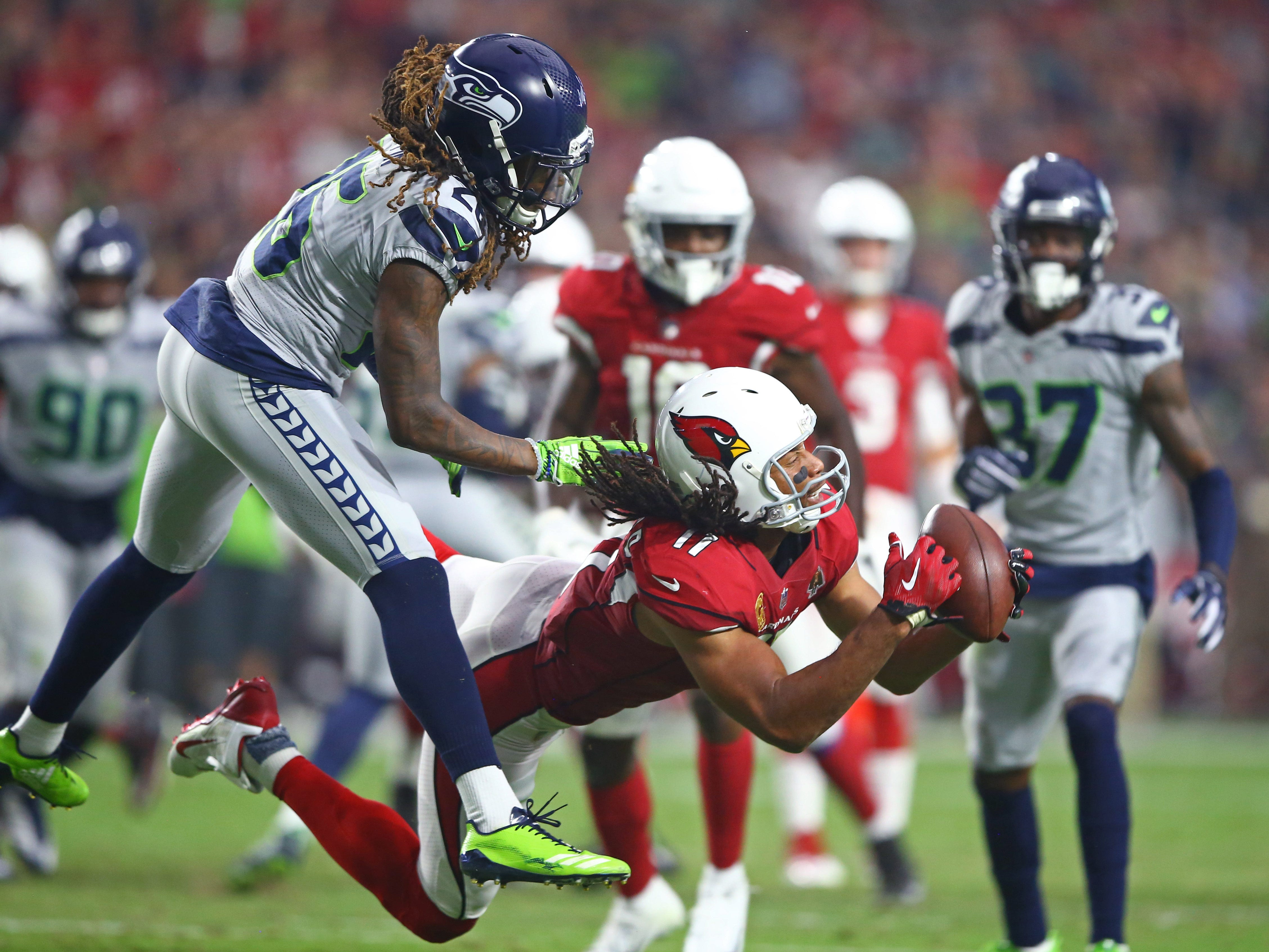 Arizona Cardinals wide receiver Larry Fitzgerald makes a diving catch against Seattle Seahawks cornerback Shaquill Griffin in the second quarter at State Farm Stadium.