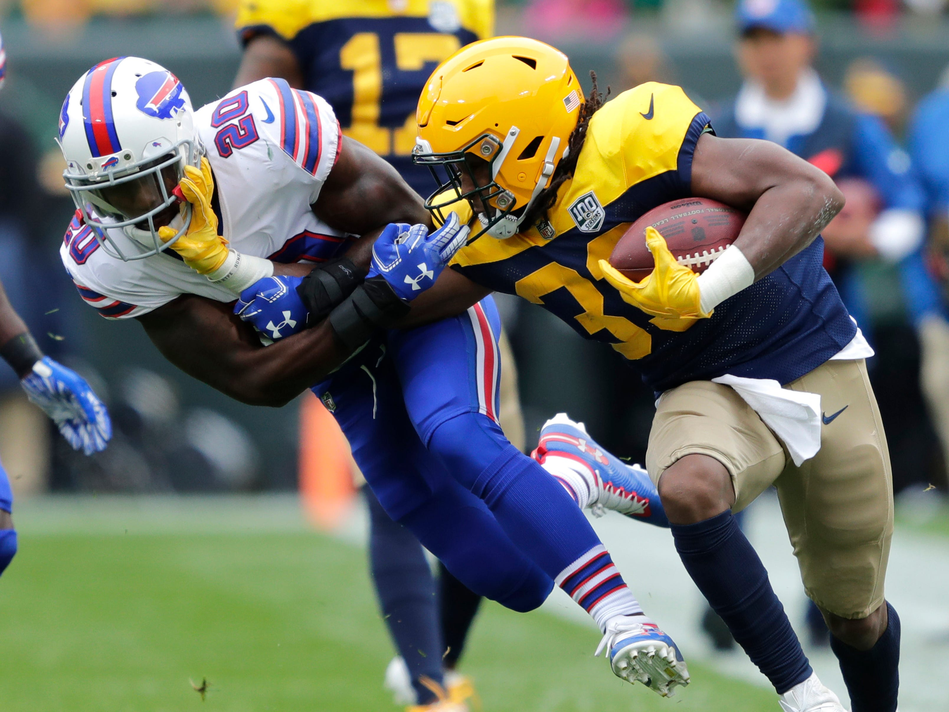 Green Bay Packers running back Aaron Jones stiff arms Buffalo Bills defensive back Rafael Bush during the first quarter at Lambeau Field.