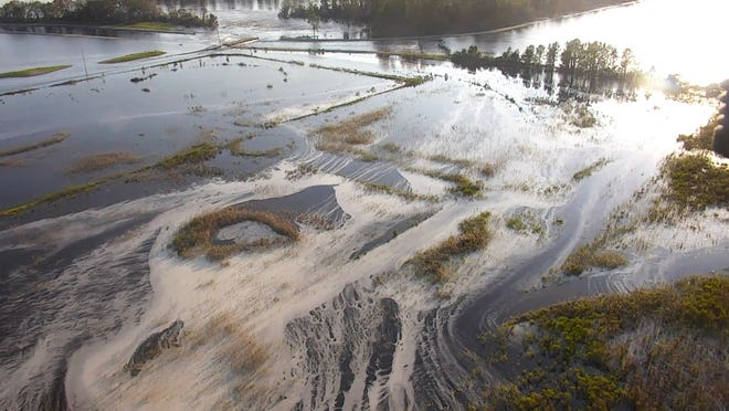 Drone video on Sept. 21, 2018, captures  gray material flowing out of a flooded coal ash dump toward the Cape Fear River in Wilmington, North Carolina.