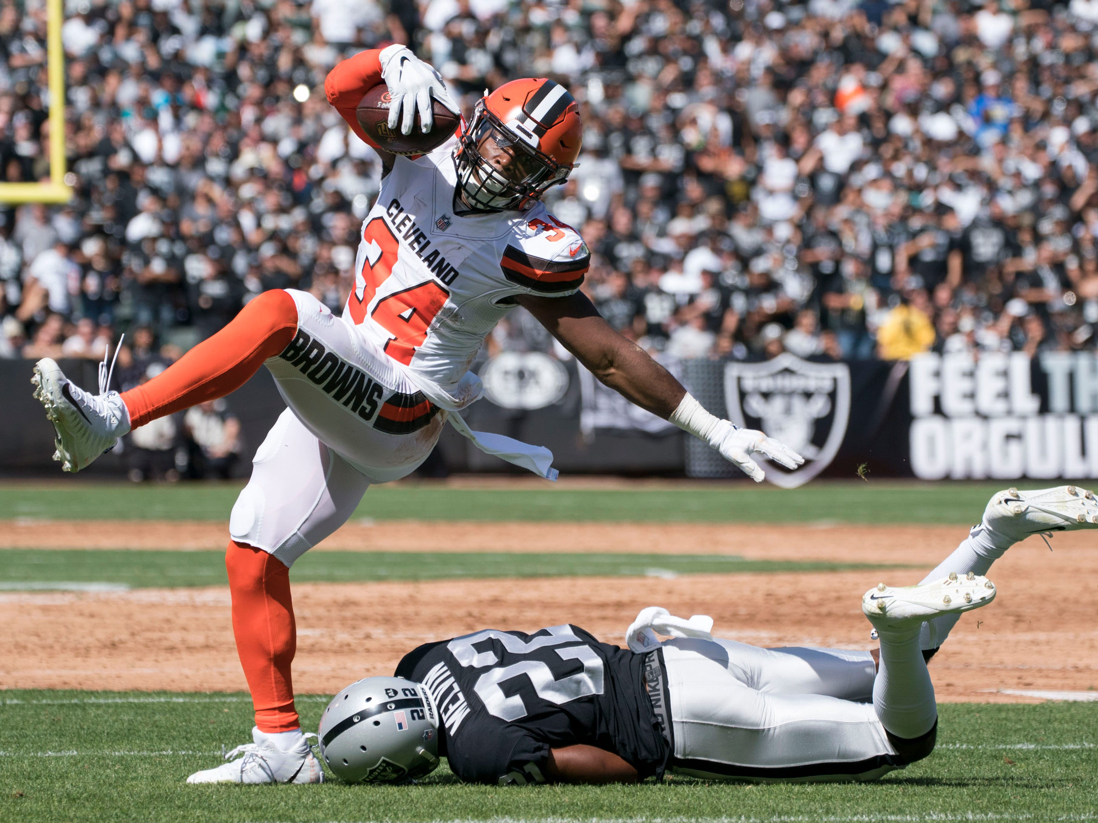 Cleveland Browns running back Carlos Hyde runs against Oakland Raiders defensive back Rashaan Melvin during the first quarter at Oakland Coliseum.