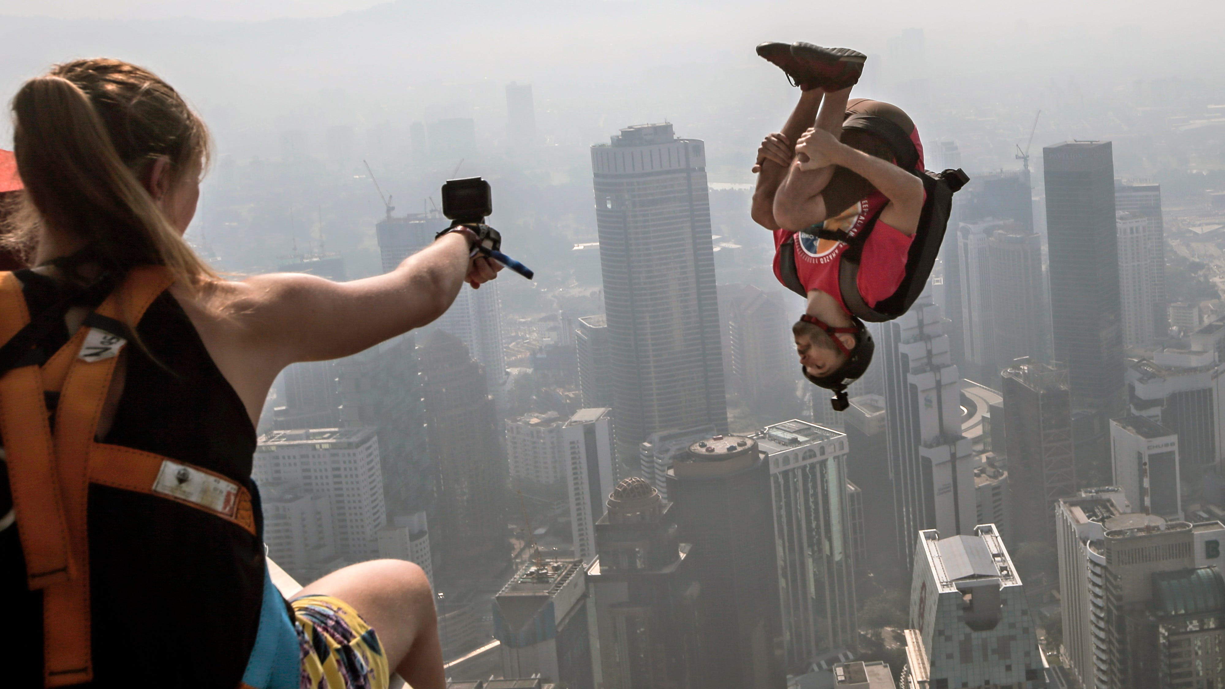 BASE jumper William Mitchell, of the United States, jumps from a nearly 1,000-foot high deck during the Kuala Lumpur Tower International Jump in Kuala Lumpur, Malaysia, Sept. 30, 2018.