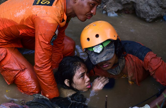 Rescuers try to free Nurul Istikharah, 15, from her damaged house following an earthquake and tsunami in Palu, Central Sulawesi, Indonesia, on Sept. 30, 2018.