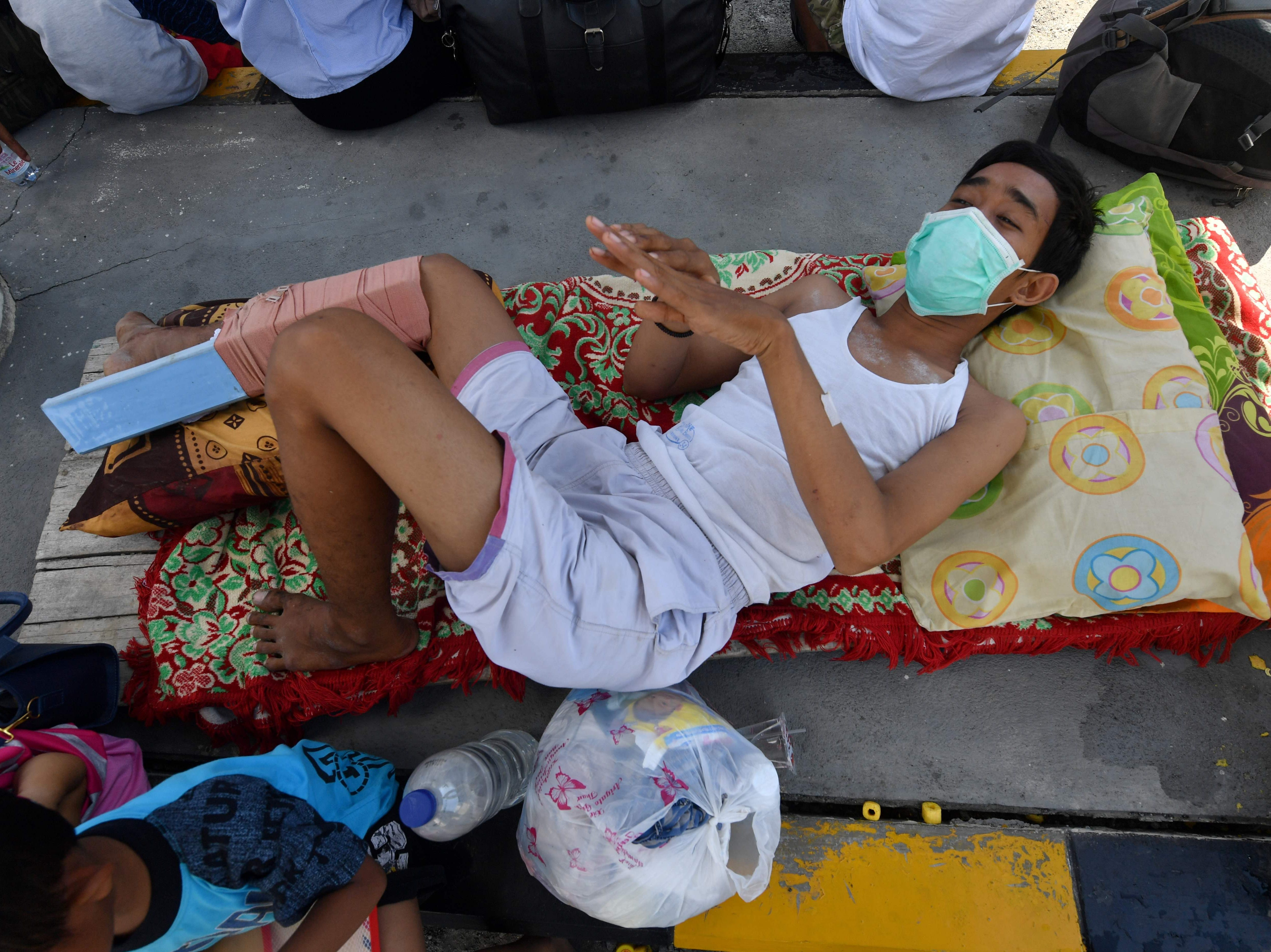 A injured man waits to be evacuated at the Mutiara Sis Al Jufri airport in Palu, Indonesia's Central Sulawesi on Sept. 30, 2018, following the Sept. 28 earthquake and tsunami.