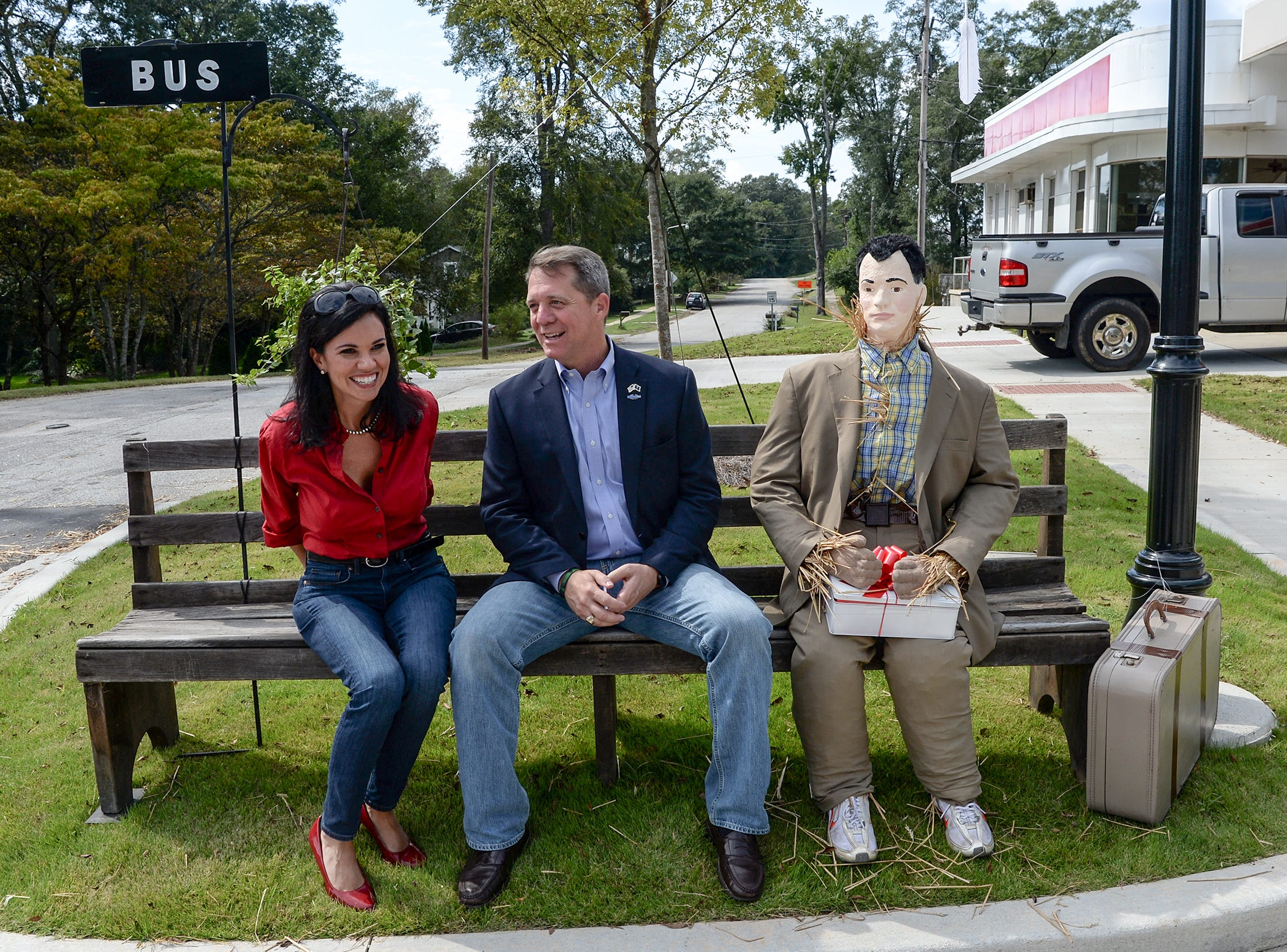 Rep. James Smith, middle, Democratic nominee for South Carolina Governor, and running mate Rep. Mandy Powers Norell stop to sit near a scarecrow version of movie character Forest Gump, as they visit in the town square in Pendleton on Monday, October 1, 2018.