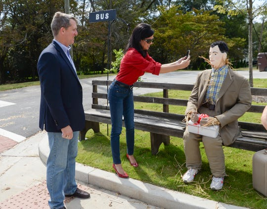 Rep. James Smith, left, Democratic nominee for South Carolina Governor, watches running mate Rep. Mandy Powers Norell get a photo of scarecrow version of movie character Forest Gump, as they visit in the town square in Pendleton on Monday, October 1, 2018.
