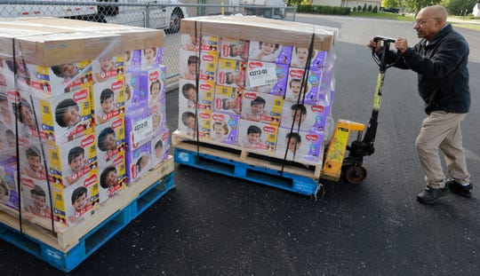 Hussain Sattar of Father Carr's Food Pantry helps position the pallets of diapers to be distributed.  The Oshkosh Area Community Food Pantry received a donation of 50 pallets with 100,400 diapers on them from Gannett Co., and Kimberly Clark Corp. in Oshkosh on Sept. 24, 2018.  The diaper were distributed to nine food pantries in the area.