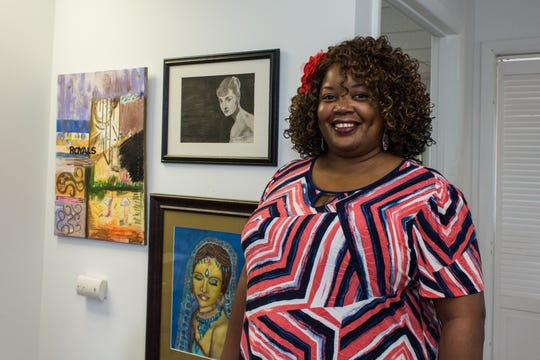Sherone Rogers stands  next to some of her artwork at Shore House in Long Branch.