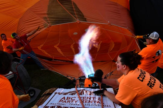 Crew members of the Cosmos I work to inflate the hot air balloon during Saturday's balloon glow.
