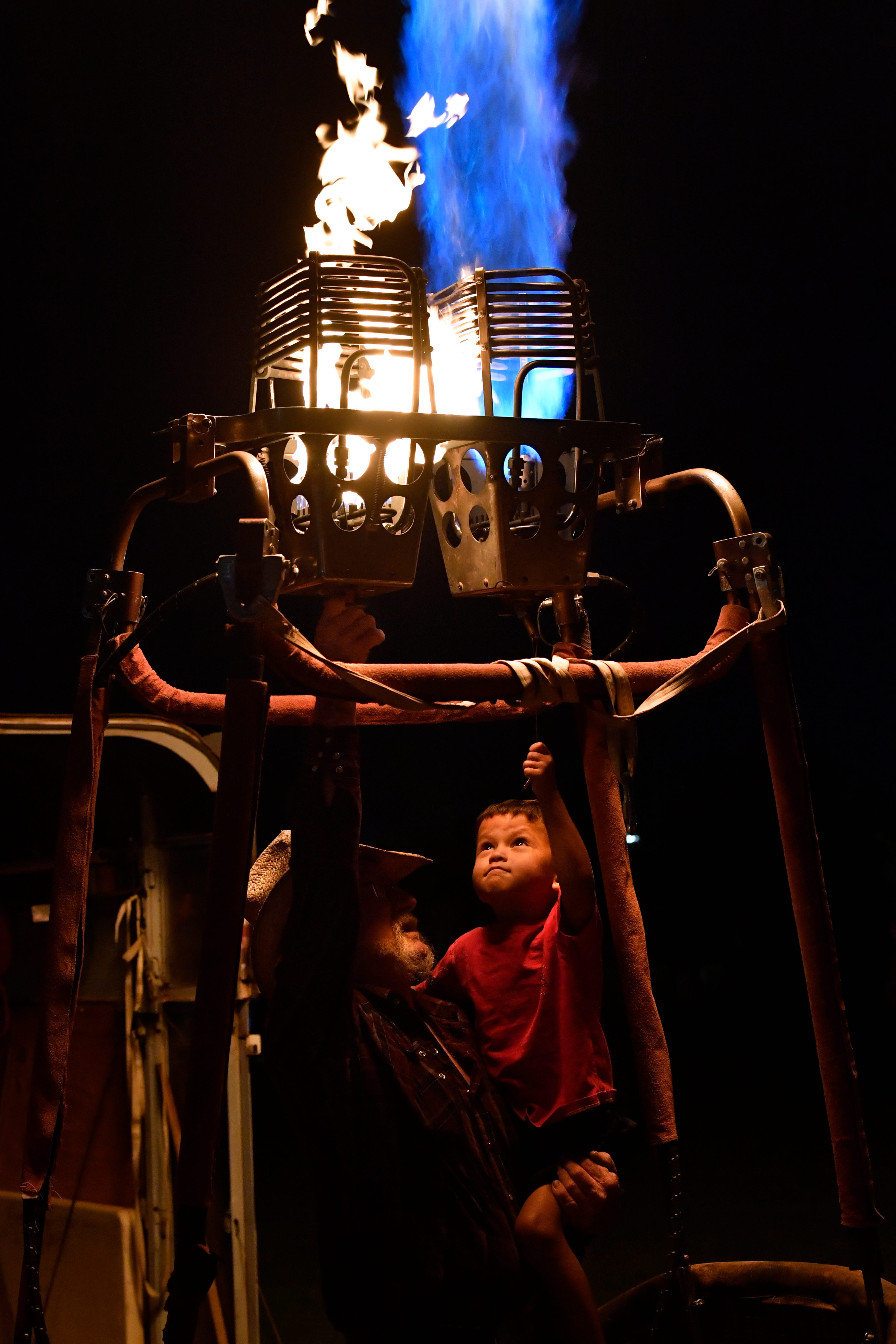 Emyrson Parker, 3, lights a burner with the help of a pilot on a gondola without its hot air balloon during Saturday's Big Country Balloon Fest in Redbud Park. The balloon glow capped the festival with several hot air balloons lighting the night.