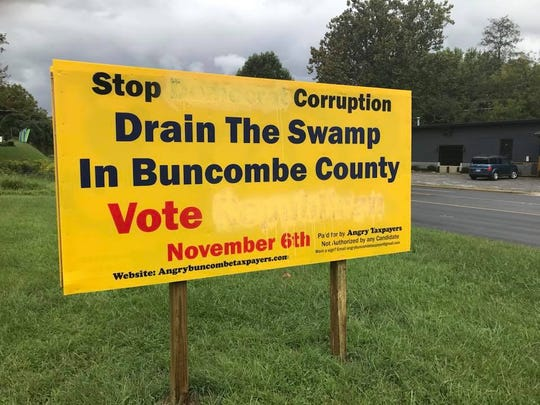 """Several signs put up by Angry Buncombe Taxpayers have been defaced or vandalized, including this one where someone painted over the word """"Democrat"""" in the """"Stop Democrat Corruption"""" line. They also painted over """"Republican"""" in the """"Vote Republican"""" line."""