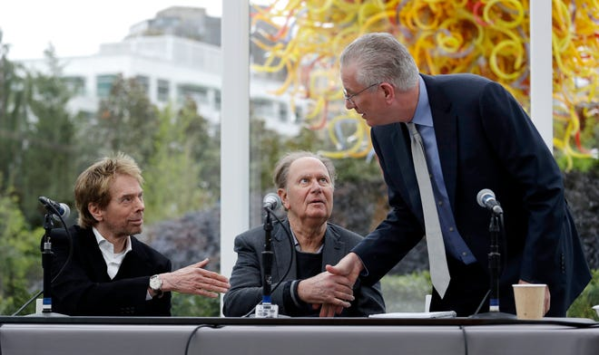 Tod Leiweke, right, greets part owners Jerry Bruckheimer, left, and David Bonderman during an April news conference at which Leiweke was named the president and CEO for a prospective NHL expansion team in Seattle. The prospective owners of an NHL expansion team in Seattle will make their pitch to an executive committee of owners in New York on Tuesday.