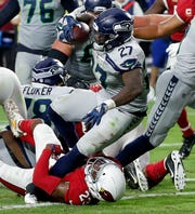 Seattle Seahawks running back Mike Davis (27) scores a touchdown over fallen Arizona Cardinals defensive back Bene' Benwikere (23).