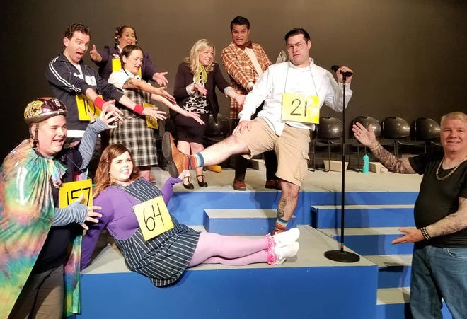 """Mason Enfinger (21), playing William Barfee, shows off the """"magic foot"""" to fellow cast members (clockwise from top left) James Sgambati, Michelle Abad, Amanda Pugh, Michelle Lorenz Odell, Mario Penalver, Dan Engelhard, Breanne Penalver and Justin Silver."""