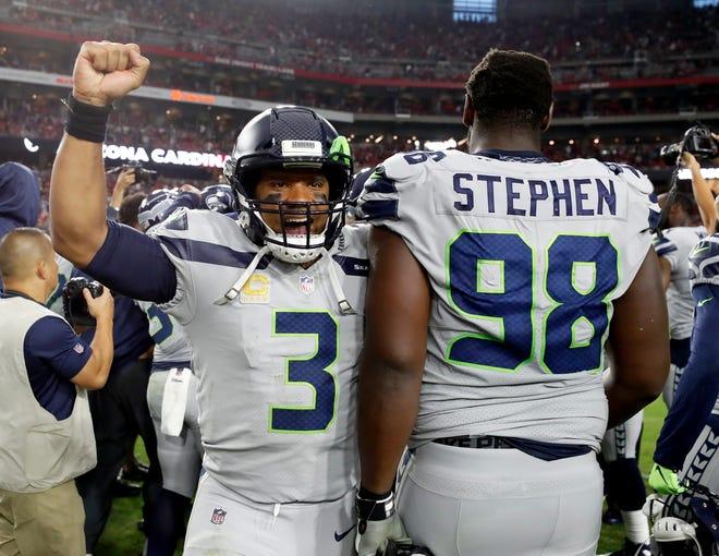 Seattle Seahawks quarterback Russell Wilson (3) celebrates with defensive tackle Shamar Stephen (98) after Sebastian Janikowski's winning field goal.
