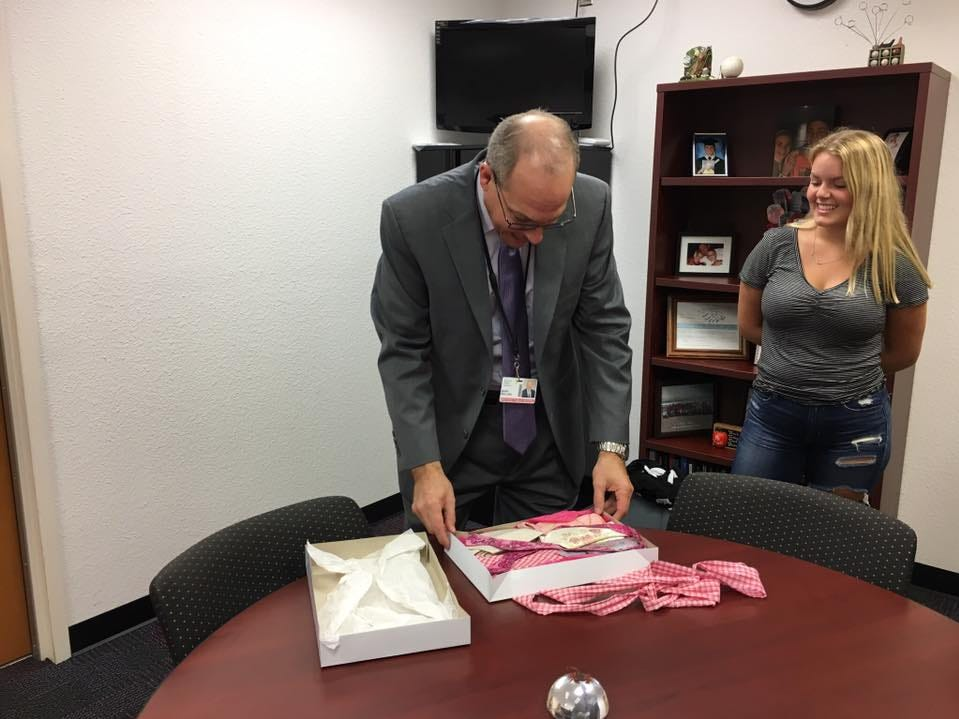 Superintendent Mark Mullins receives ties from Satellite High fashion design students.