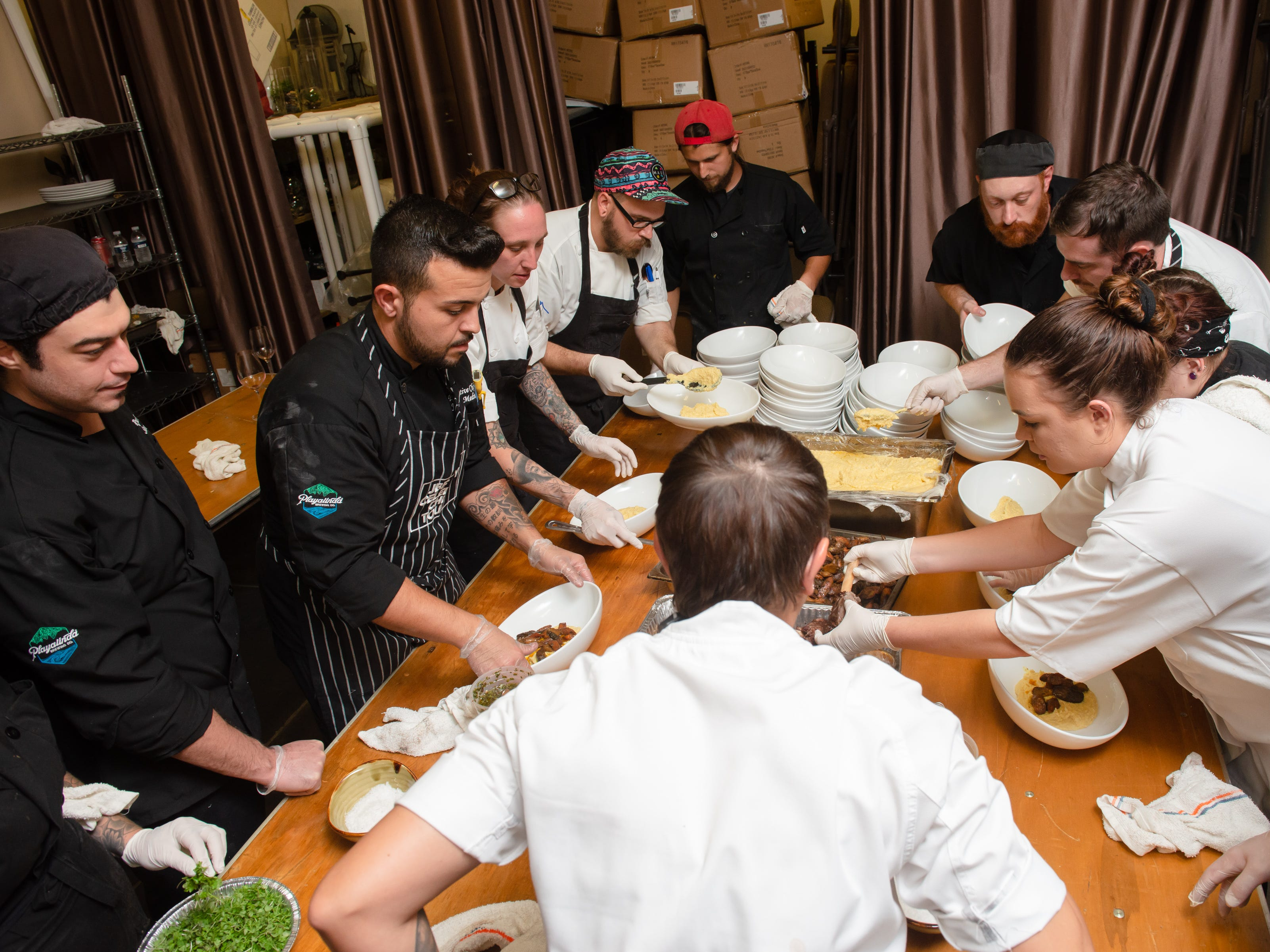 Chefs work together on the main dish at the James Beard Foundation Celebrity Chef Dinner held at the Brevard Zoo. (Photo by Amanda Stratford, for FLORIDA TODAY)