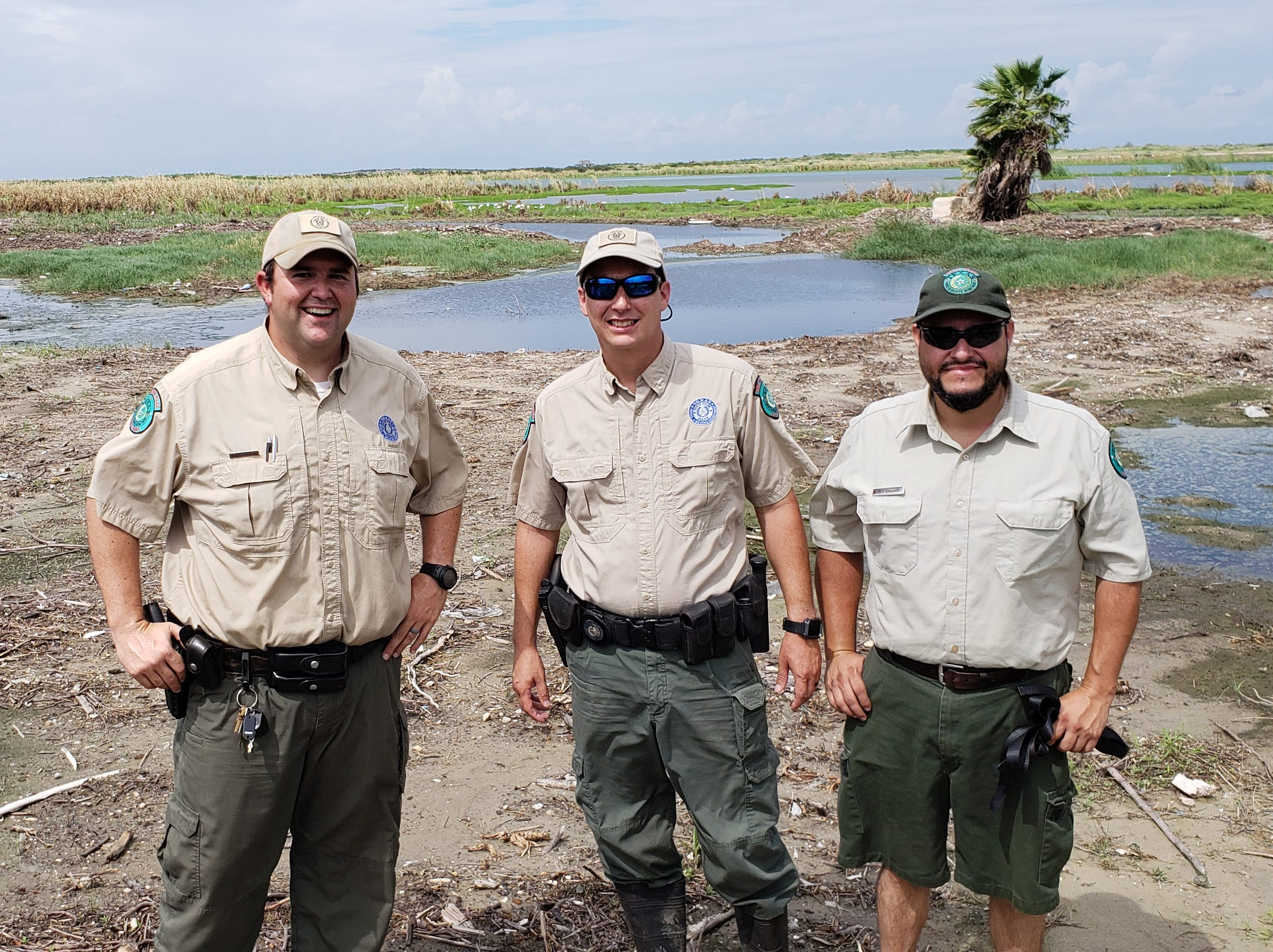 Officials with Mustang Island State Park relax after capturing and releasing a 12-foot alligator in Port Aransas. Notice the gator on the left in the background. That's Park Superintendent Scott Taylor, on left, park police officer Jeremiah Rodriguez, center, and Joseph Aregon, assistant superintendent.