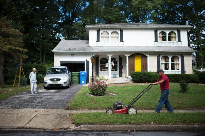 Korean immigrant Daegil Lee, 71, cuts grass at the home of Korean War veteran William Guerriero in Cherry Hill.