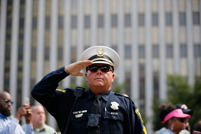 Officer Hank Ward salutes as the National Anthem is sung during a Cincinnati Police Department awards ceremony at Fountain Square Monday, October 1, 2018 to honor those who assisted with the efforts to secure the scene and assist injured victims of the Fifth Third Center shooting last month.