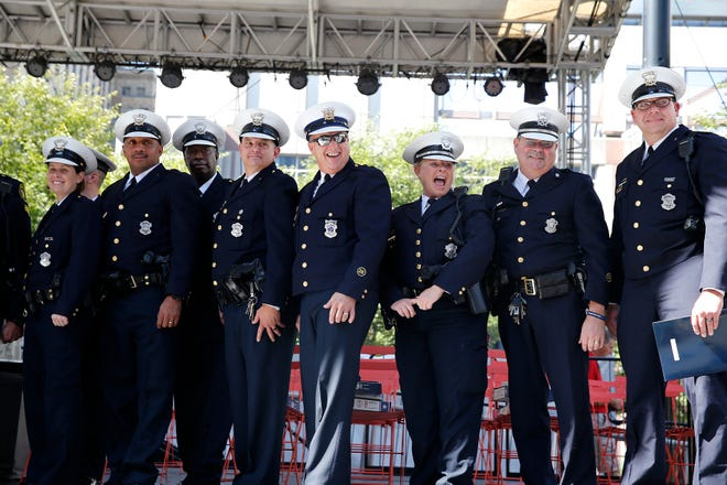 Members of the Cincinnati Police Department look at family and friends after being honored for their service during the Fifth Third Center shooting last month. Several CPD officers received awards, along with a member of the Hamilton County Sherriff Department, civilians and a dispatcher. The ceremony took place at Fountain Square Monday, October 1, 2018.
