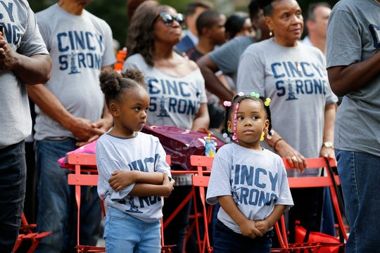 Kira Bettis, 4, left, and Bella Reynolds, 3, listen to the singing of the National Anthem during a Cincinnati Police Department awards ceremony at Fountain Square Monday, October 1, 2018.  The girls along with other family members were there to support CPD officer Antonio Etter who received the Award of Valor as part of the team who engaged the gunman during the Fifth Third Center shooting last month.