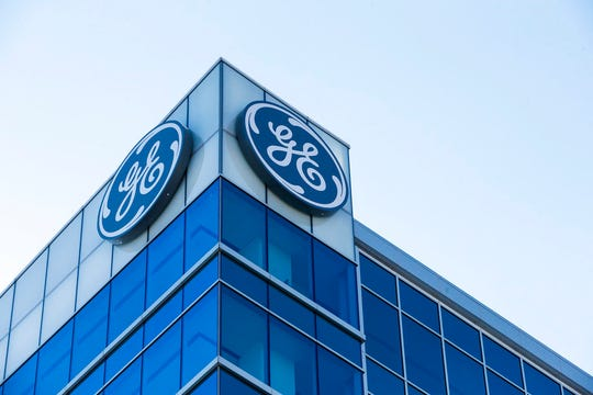 FILE- In this Jan. 16, 2018, file photo, the General Electric logo is displayed at the top of their Global Operations Center in the Banks development of downtown Cincinnati. Industrial giant General Electric is naming H. Lawrence Culp Jr. as its chairman and CEO. Culp, former CEO and president of Danaher Corp., succeeds John Flannery in the posts.  (AP Photo/John Minchillo, File)