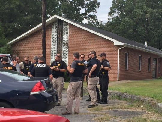 Law enforcement officers gather to share updates on the manhunt for Kirby Wallace on Monday at the search command headquarters, at the Church of Christ at Needmore.