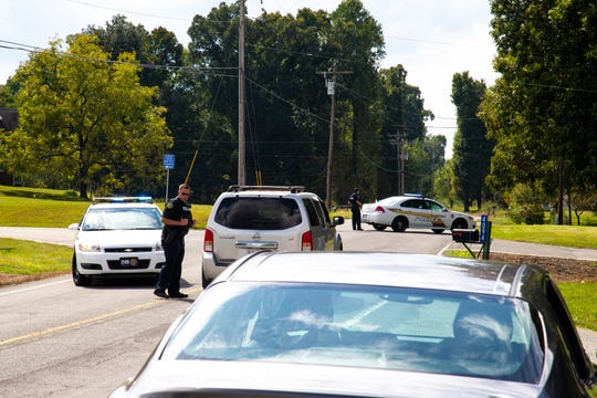 Police officers direct traffic away from the roadblock at Lylewood Road during a manhunt Monday, Oct. 1, 2018, in Woodlawn, Tenn.