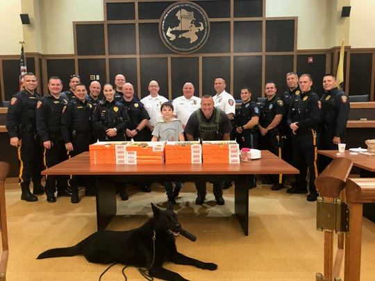 """With a goal of meeting every police officer in the U.S., """"Donut Boy,""""akaTyler Carach, 10, brought his superpowers of respect and kindness — and the gift of donuts — to the Bridgewater police department the morning of Sept. 23. In the township municipal courtroom, Tyler, who wants to be a K-9 officer, and his mother Sheena Carach met up with a dozen members of local police departments."""