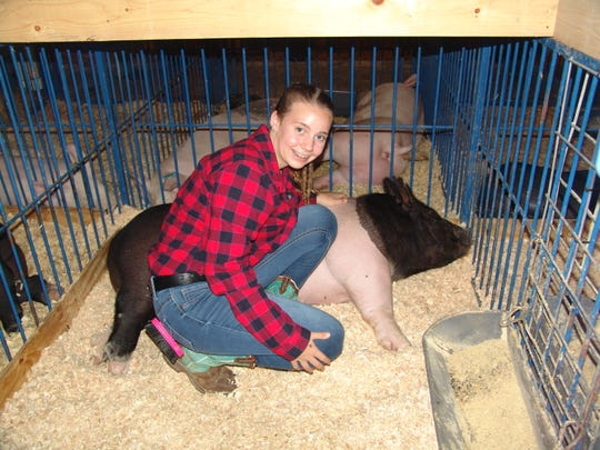 Jordyn Aronhalt poses with her hog, Goofy, in the hog barn on Sunday at the Coshocton County Fair.