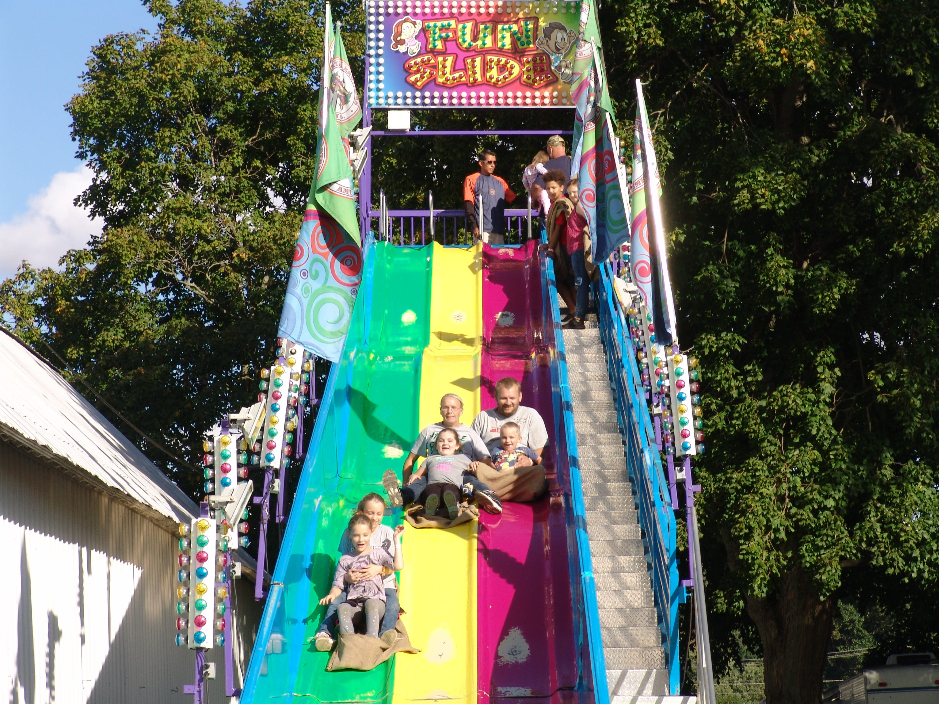 A group of fair-goers take a ride on the Fun Slide Saturday evening at the Coshocton County Fair.