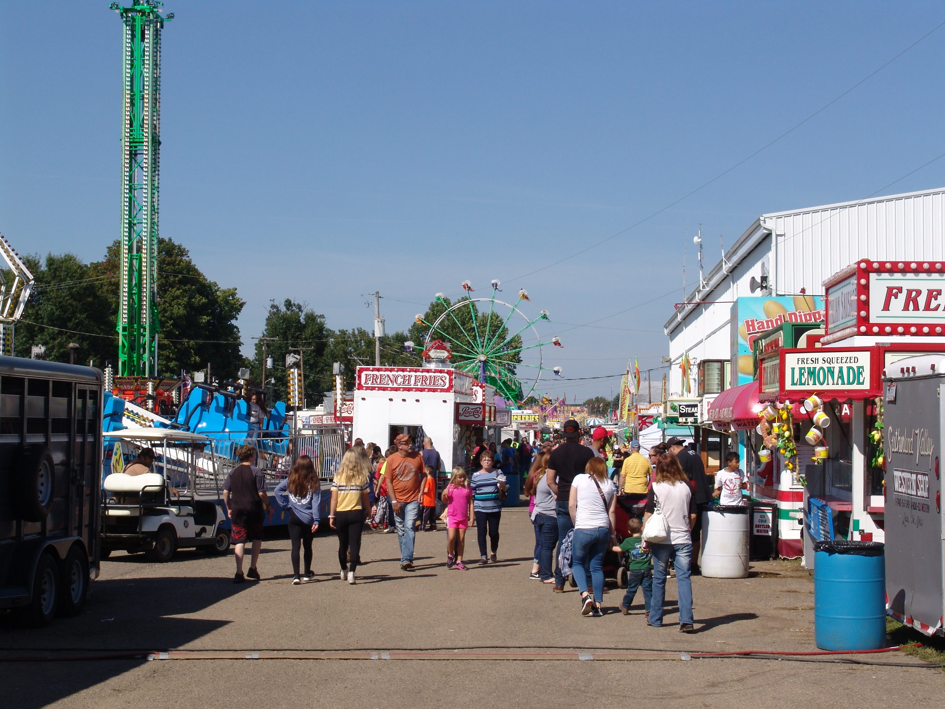 Fair goers stroll the midway Sunday at the Coshocton County Fair.
