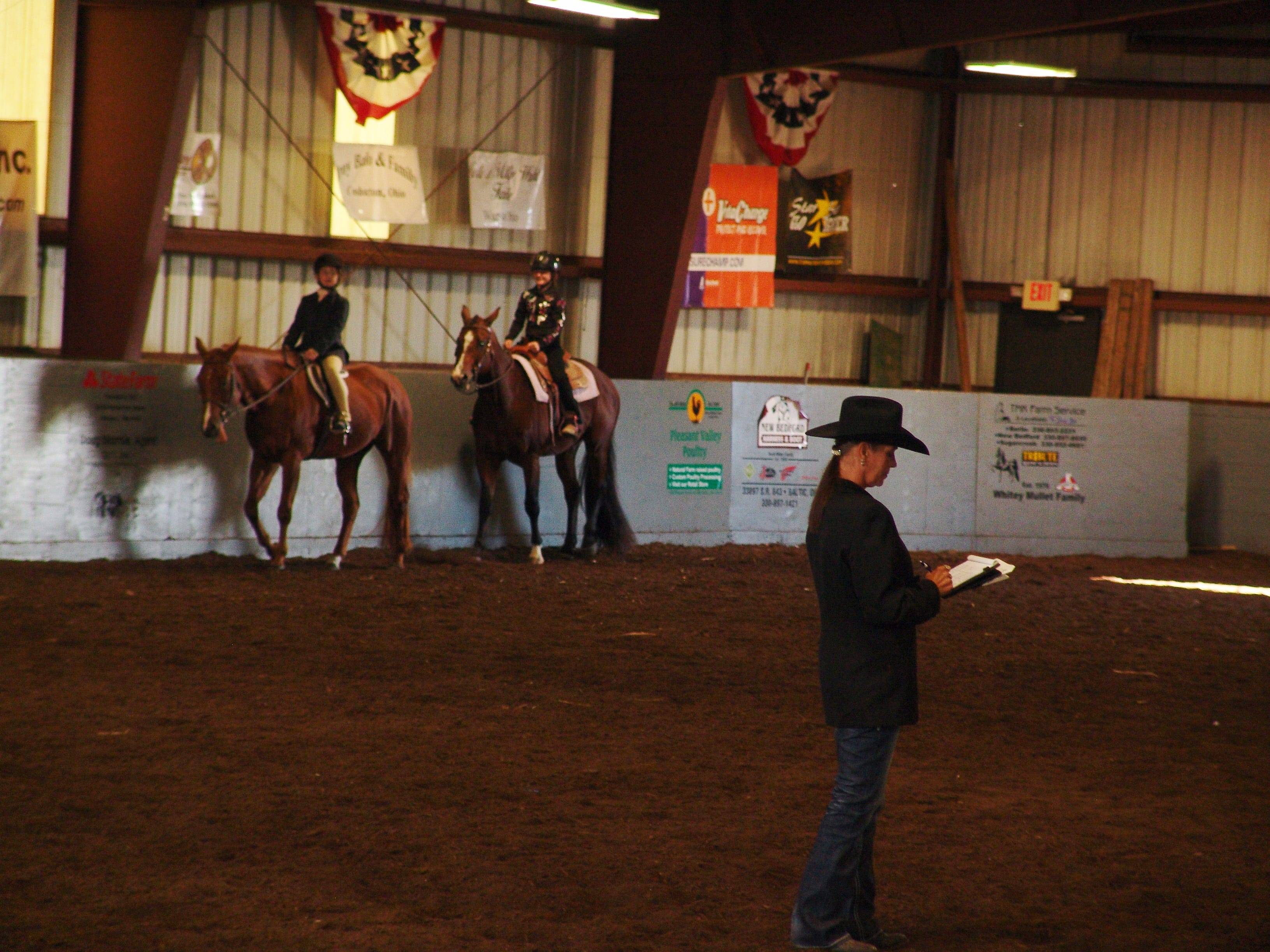 A judge evaluates exhibitors during the walk/trot category of the horse show.