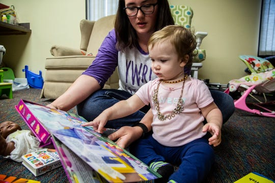 Rachel Scrivner, 20 of Osceola, reads a book to her 15-month-old daughter Delilah on Monday, Oct. 1, 2018, at the Young Women's Resource Center in Des Moines. Scrivner drives from Osceola to Des Moines twice a week to take advantage of the resources YWRC provides for mothers like her.