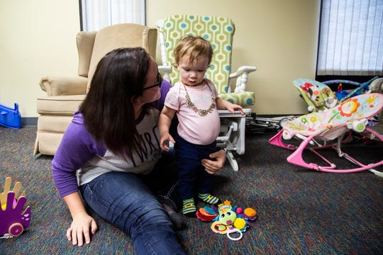 Rachel Scrivner, 20 of Osceola, holds her daughter Delilah as she stands among a room full of toys at the Young Women's Resource Center on Monday, Oct. 1, 2018, in Des Moines.