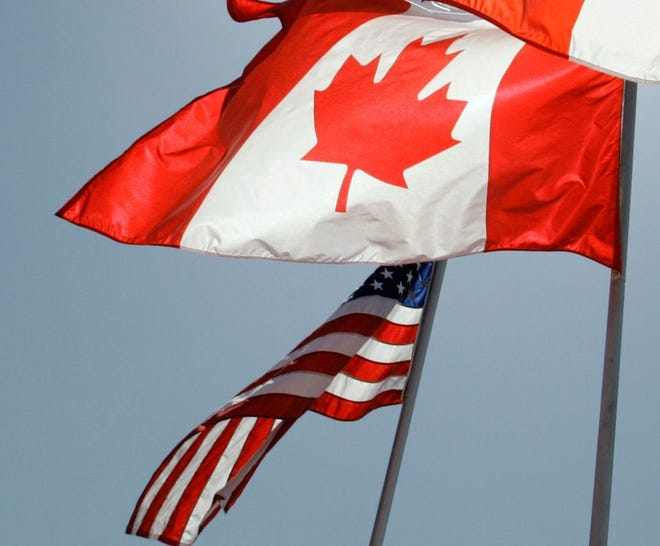 National flags representing the United States and Canada fly in the breeze.