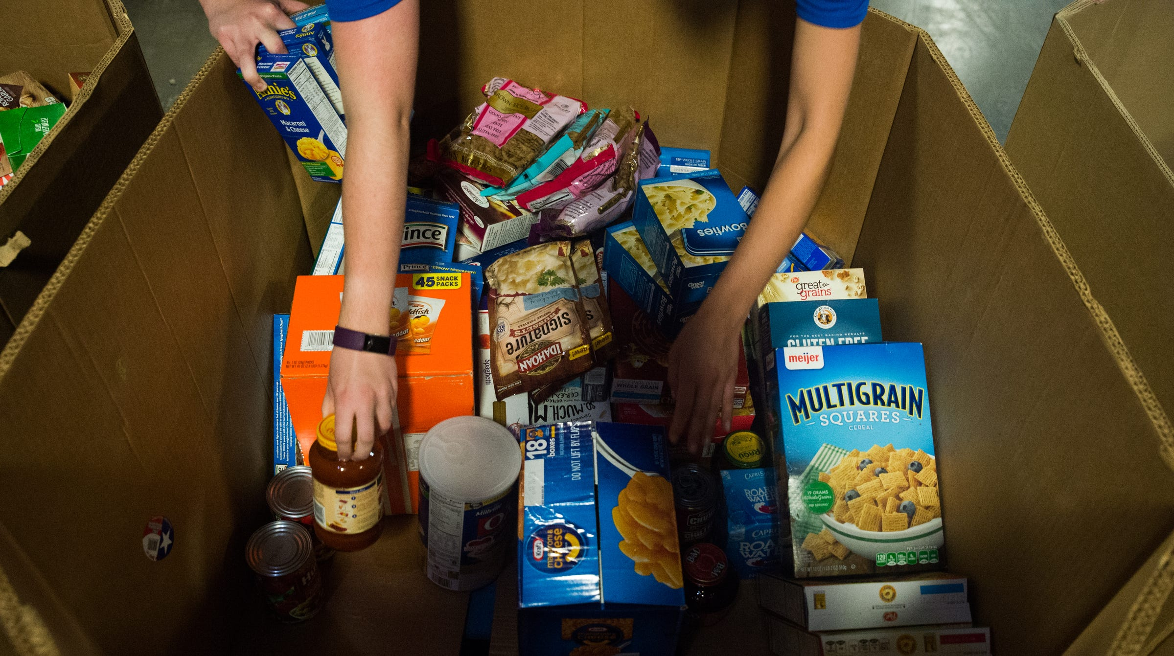 Ford interns pack food into boxes at Gleaners Food Bank in Detroit on July 3.