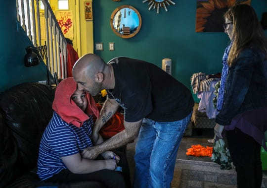 Charlie Kondek, of Northville helps his son, Samuel, who is autistic, get up from the couch as his wife Laurie looks on at their home on Friday, Sept. 28, 2019.